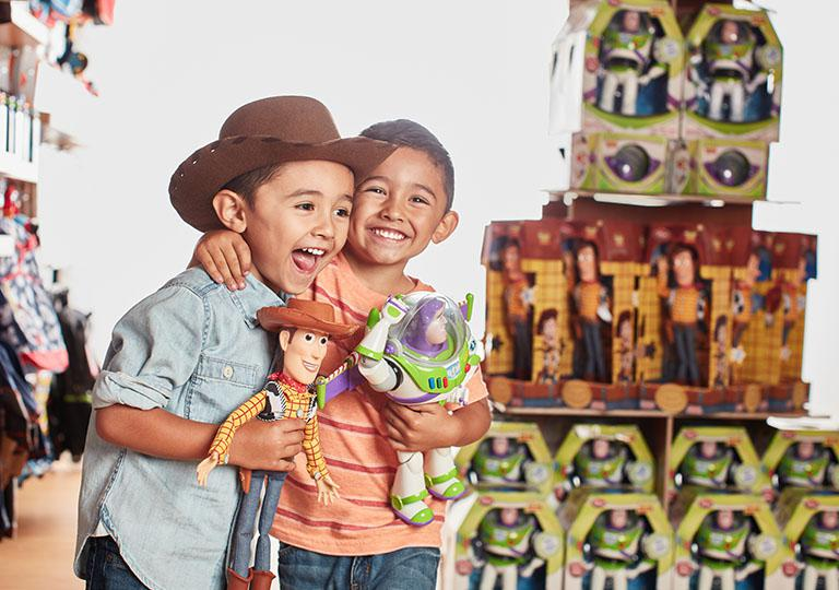 Children in Disney Store with Woody and Buzz Lightyear Action Figures
