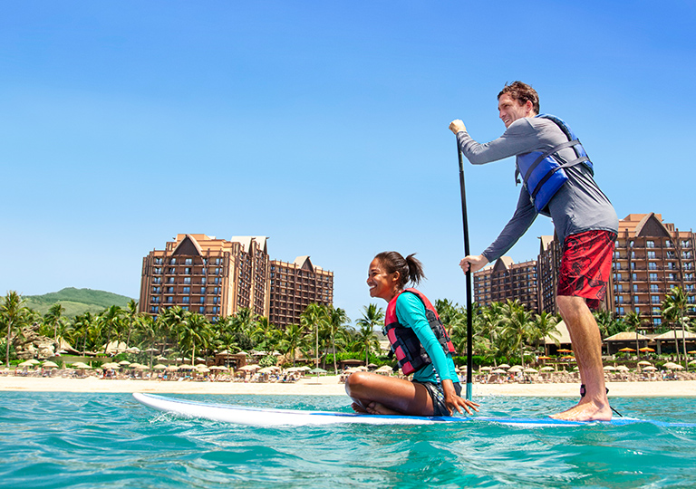 Couple paddling across the water at Aulani in Hawaii