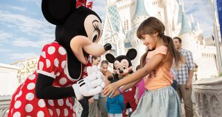 young girl excited to meet Minnie while family meets Mickey