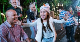 Excited girl wearing and Olaf hat with her family