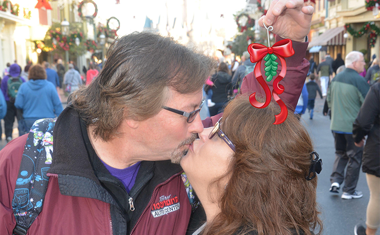 Couple at Disney kissing under mistletoe