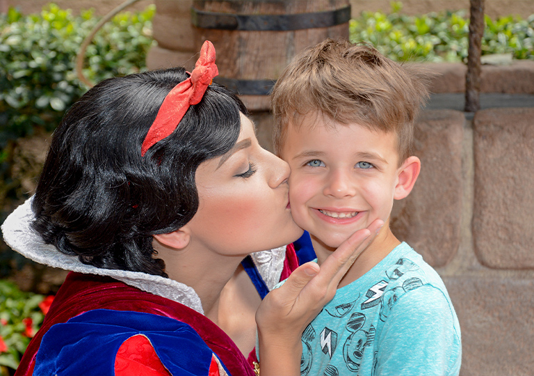 Boy getting a kiss from Snow White