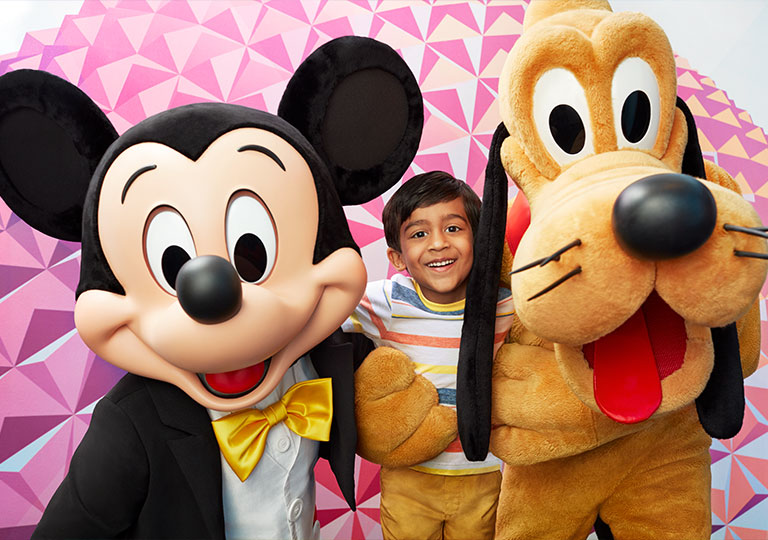 boy posing with Mikey and Pluto Disney