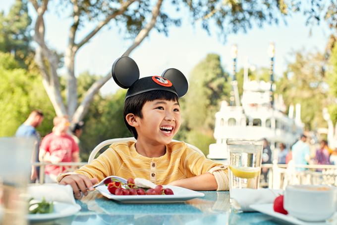 Boy eating with Mickey Mouse hat on