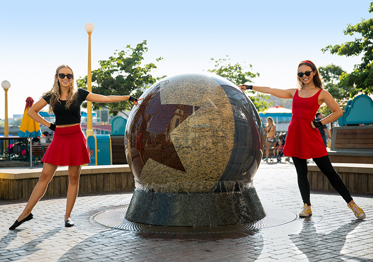 Girls posing next to Pixar Pier fountain